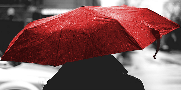 """A person walks while holding a red umbrella"""
